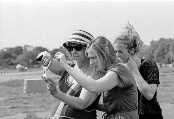 a black and white photograph of a woman with dark glasses and head holding a camera. Two younger women help her to take the picture.