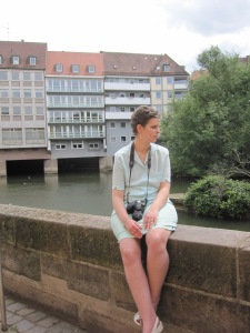 Nadine sitting on a low wall with houses and trees in the background.