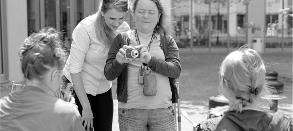 black and white photo of a blind and a sighted woman positioning a camera to photograph another woman in front of them together.