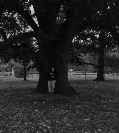 Total view: person standing in front of a tree