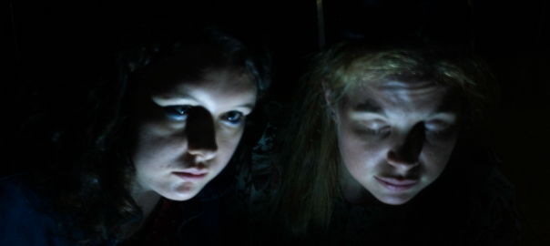 Light painting of 2 women's faces lit from below, in front of a black background