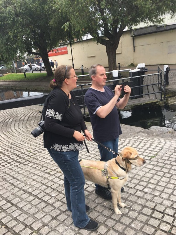 a man with with a guide dog taking pictures, a woman standing next to him assists